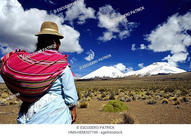 Bolivia, Oruro Department, Sajama Province, Sajama National Park, Aymara Indian woman facing Pomerape and Parinacota volcanoes