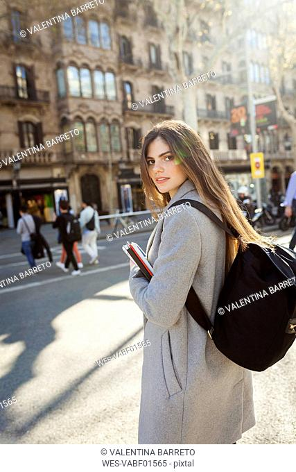 Spain, Barcelona, portrait of young woman with backpack standing at street