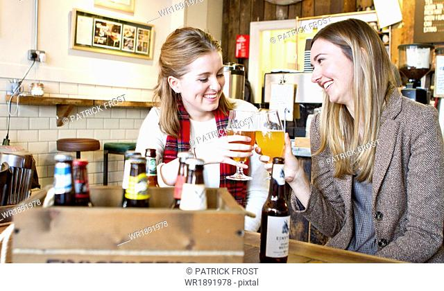 Young women toasting with beer in pub, Dorset, Bournemouth, England