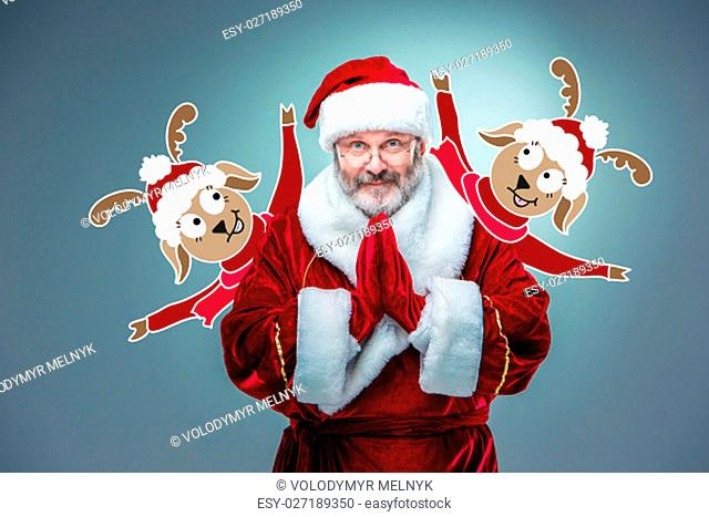 A happy, smiling Santa Claus in glasses with hands in Thai greeting on a blue background