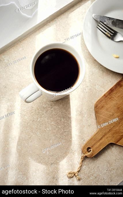 A woman's hand holding a white mug with coffee in a sunstreaked kitchen