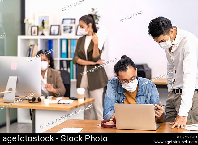Group of interracial business worker team wear protective face mask in new normal office with social distance practice with hand sanitiser alcohol gel on table...