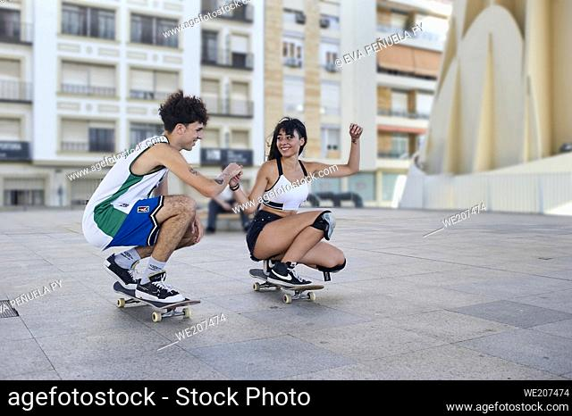 Two young people riding on skateboard in the city
