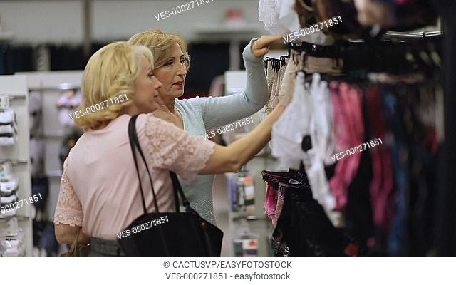 Smiling women doing shopping in clothes store