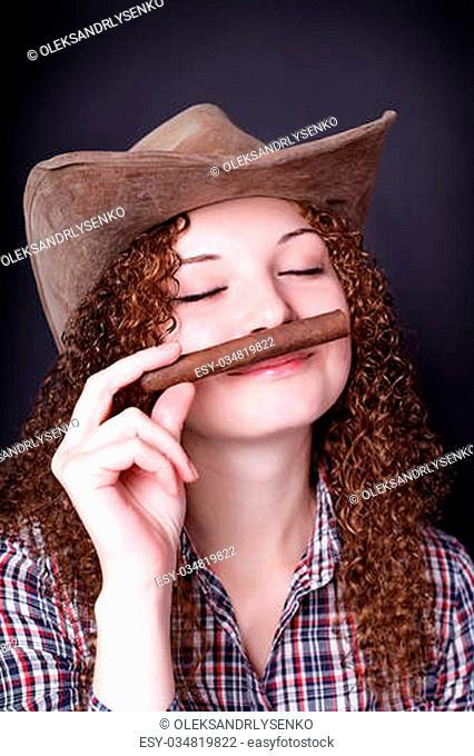 pretty redhead girl smelling cigar dark background