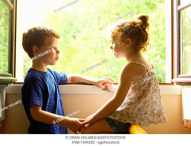 A brother and sister talking to each other by a window