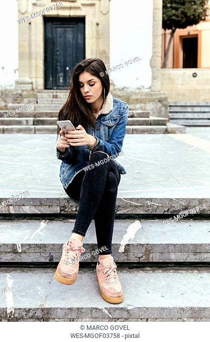 Young woman sitting on stairs in a town checking her smartphone