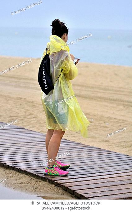 Girl with raincoat,  triathlon competition, Barcelona, Catalonia, Spain