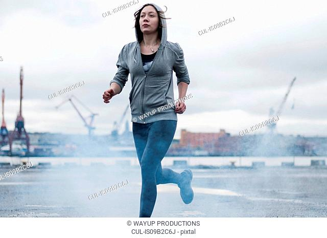 Young female runner running on stormy dockside