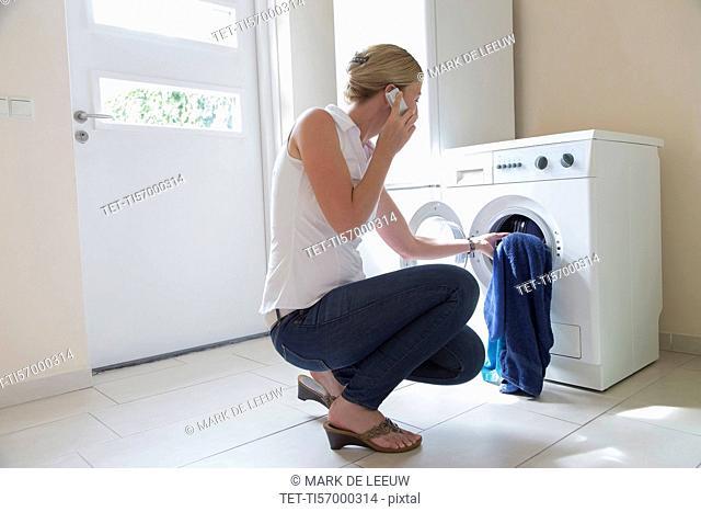 Woman taking laundry out of washing machine
