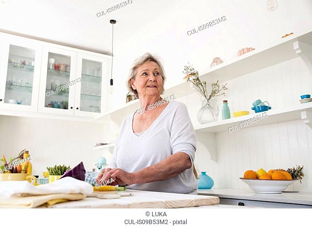 Senior woman looking over her shoulder while preparing vegetables at kitchen table
