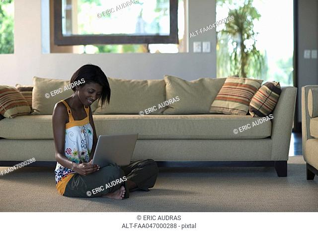 Young woman sitting on living room floor using laptop computer