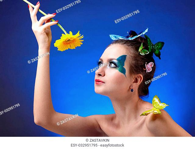 portrait of beautiful model with butterfly bodyart and artificail butterflies on her finger and hair, holding flower in her hands