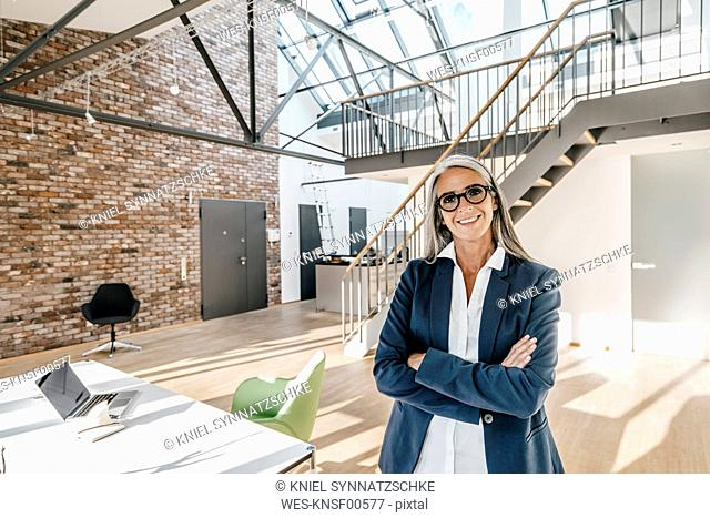 Smiling businesswoman with long grey hair standing in modern office