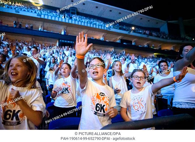 """14 June 2019, Berlin: Pupils stand singing and dancing in the grandstand of the Mercedes-Benz Arena during the concert of """"""""6K United! The choir concert is part..."""