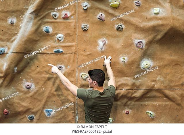 Young man in front of a climbing wall