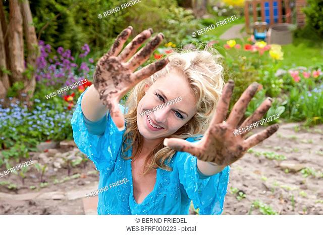 Germany, Brandenburg, Portrait of mid adults woman with dirty hands in garden, smiling