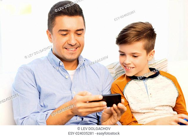leisure, technology, technology, family and people concept - happy father and son with smartphone texting message or playing game at home