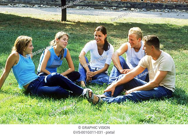 A group of young people sitting on a lawn