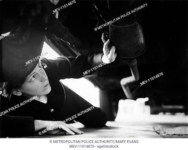 Woman police officer (Deirdre O'Donoghue) checking under a car, probably during driving training