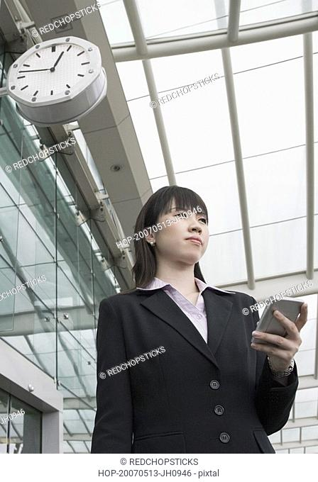 Low angle view of a businesswoman holding a personal data assistant at an airport lounge