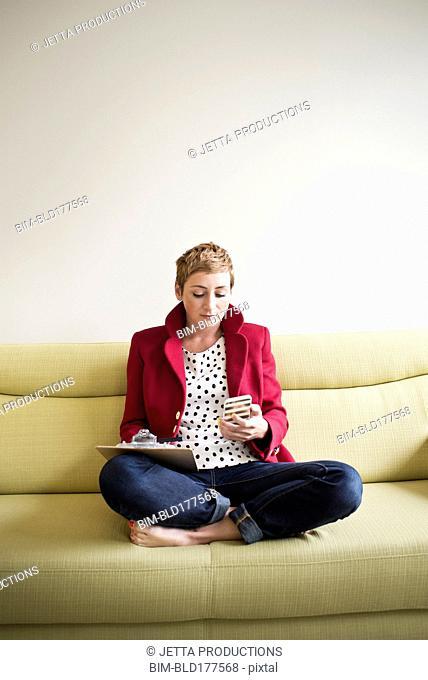 Caucasian businesswoman using cell phone on sofa