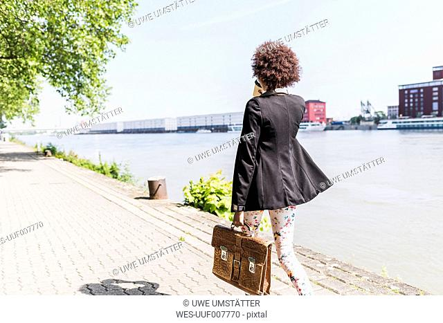 Germany, Mannheim, back view of young businesswoman with briefcase and coffee to go walking at riverside