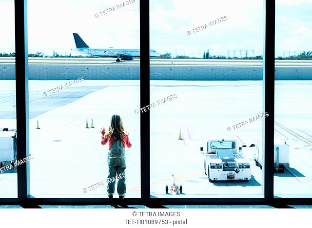 Girl (2-3) looking through window at airport