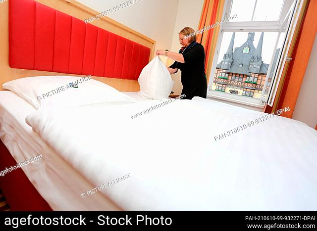 27 May 2021, Saxony-Anhalt, Wernigerode: Doreen Wieland prepares a room at the Hotel Weißer Hirsch before the reopening. Among other industries