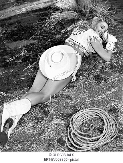 Smiling cowgirl lying on ground All persons depicted are not longer living and no estate exists Supplier warranties that there will be no model release issues