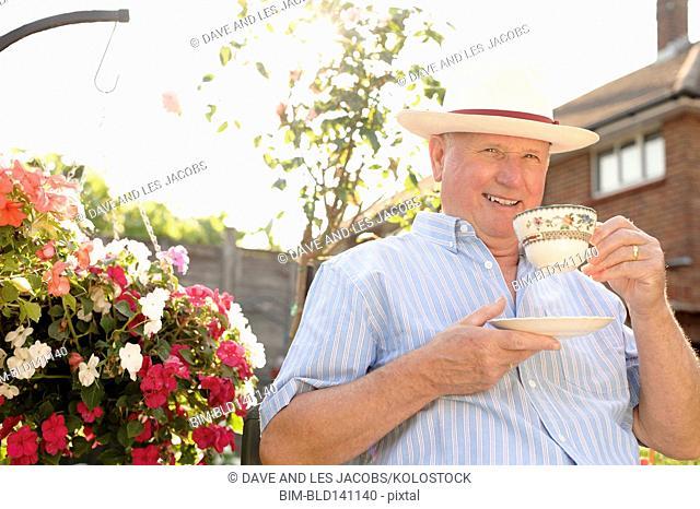Caucasian man drinking cup of tea in backyard