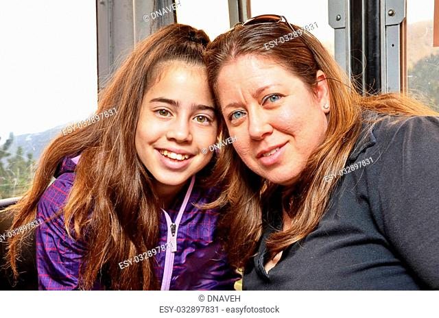Portrait of mother and daughter hugging having fun in a cable car while touring the Spanish Pyrenees