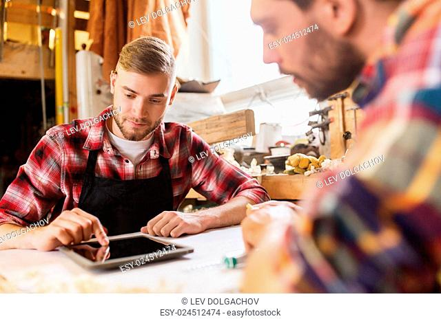 profession, technology and people concept - two workmen with tablet pc computer and blueprint at workshop