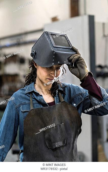 Portrait of woman wearing apron and welding mask standing in metal workshop