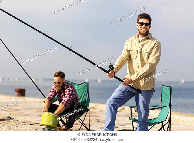 male friends with fishing rods on sea pier