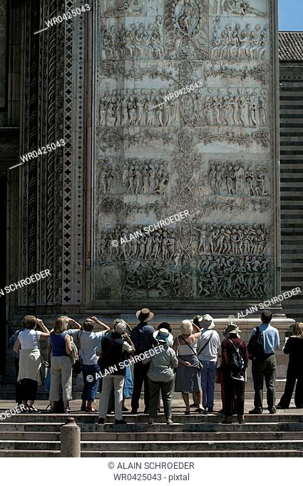 Tourists looking at stone carvings on a cathedral wall depicting purgatory and hell, Duomo Di Orvieto, Orvieto, Umbria, Italy