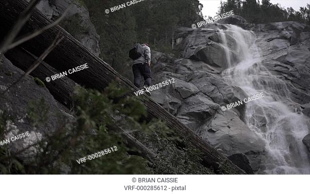 Low angle tracking shot of man walking on log towards waterfall, Squamish, British Columbia, Canada