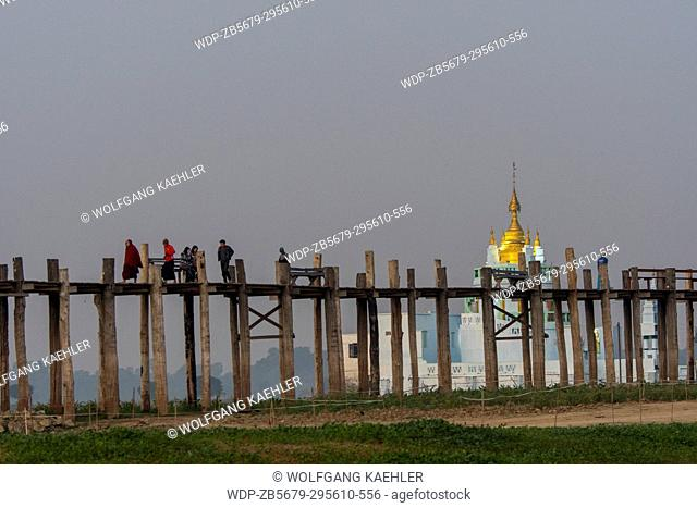 People walking before sunrise on U Bein Bridge (built around 1850 and is believed to be the oldest and longest teakwood bridge in the world) in Mandalay