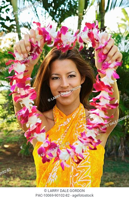 Hawaii, Oahu, Local girl wearing a yellow pareo holds out a lei, traditional welcome