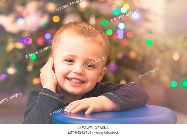 Happy and smiling cute Caucasian boy portrait with the Christmas tree in the background