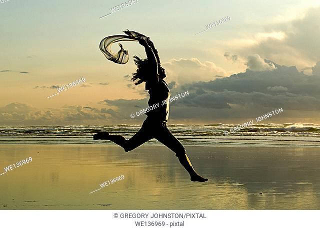 A woman with a scarf leaps on the beach in Newport, Oregon