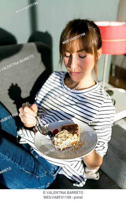 Young woman eating piece of vegan cake