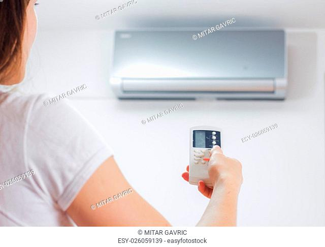 Air Conditioner , woman hand with remote control, adjustment temperature, at home