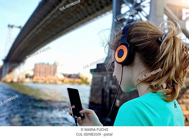 Young woman beside river, wearing headphones, using smartphone, rear view, New York City, USA