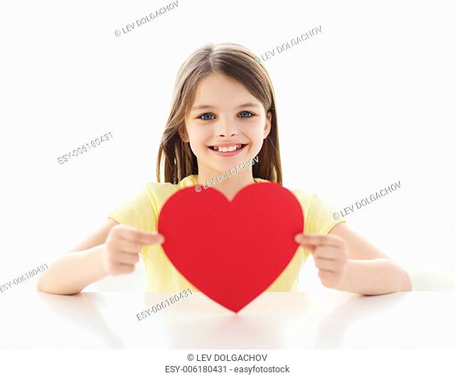 love, home, happiness and people concept - smiling little girl with red heart at home