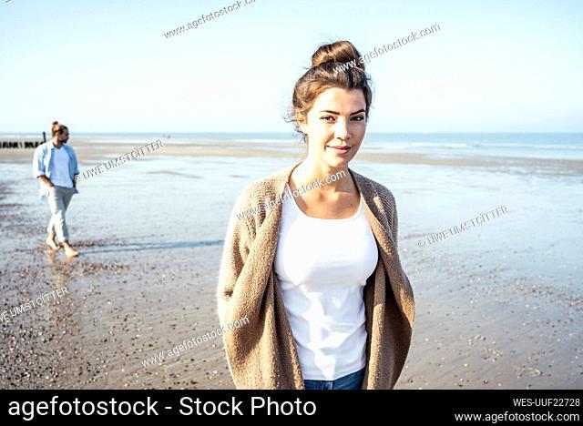 Girlfriend at beach with boyfriend in background during weekend