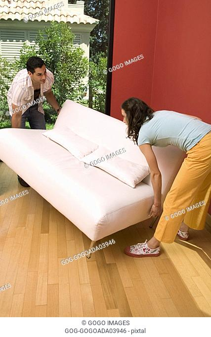 Couple setting couch down gently