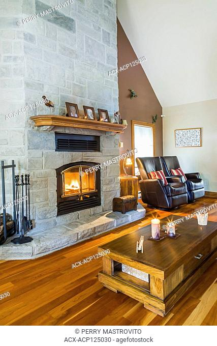 Grey cut stone lit fireplace in living room with brown leather reclining armchairs, timber wood coffee table, and cherrywood floorboards inside an old 1877...
