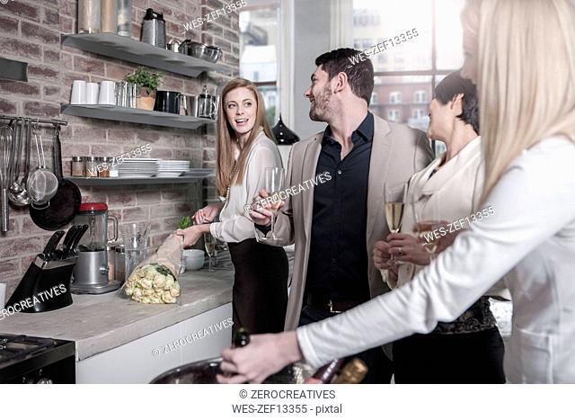 Friends holding champagne glasses socializing in kitchen