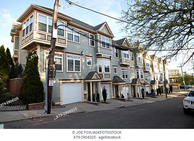 row of three storey townhouses with garages on south sydney street savin hill flats Boston USA